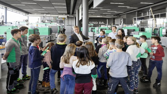 Gerhard Boehm, Managing Director Sales and Service at Arburg, explained to the children from Dauchingen how an injection moulding machine produces trowels from plastic granules.
