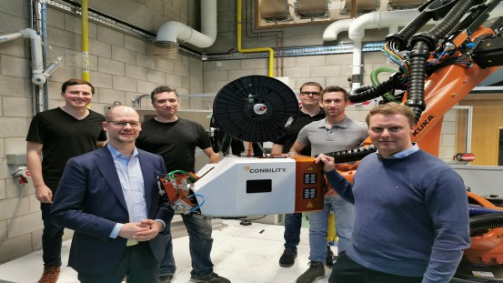 "Tape Placement Applicator ""PrePro 3D"" at the Technical Center of the University of Limerick in Ireland.  Front from right: Dr. Ronan O'Higgins (University of Limerick) and Dr. Michael Emonts (Managing Partner and Co-Founder of Conbility GmbH); Back from right: Dr. Thomas Weiler (Conbility GmbH), Markus Eckert (Fraunhofer IPT), Wolfgang Moll (Conbility GmbH), Benjamin Joemann (Conbility GmbH)"
