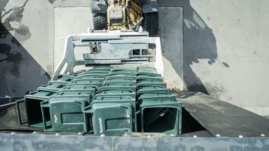 The garbage cans are fed into the shredder through the slatted curtain of the doghouse hopper attachment.
