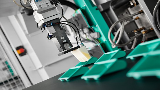 Production equipment in hard/soft combination: A customised  2-component gripper made from PC/ABS with expandable TPU has been specially designed for the removal of injection moulded handles.